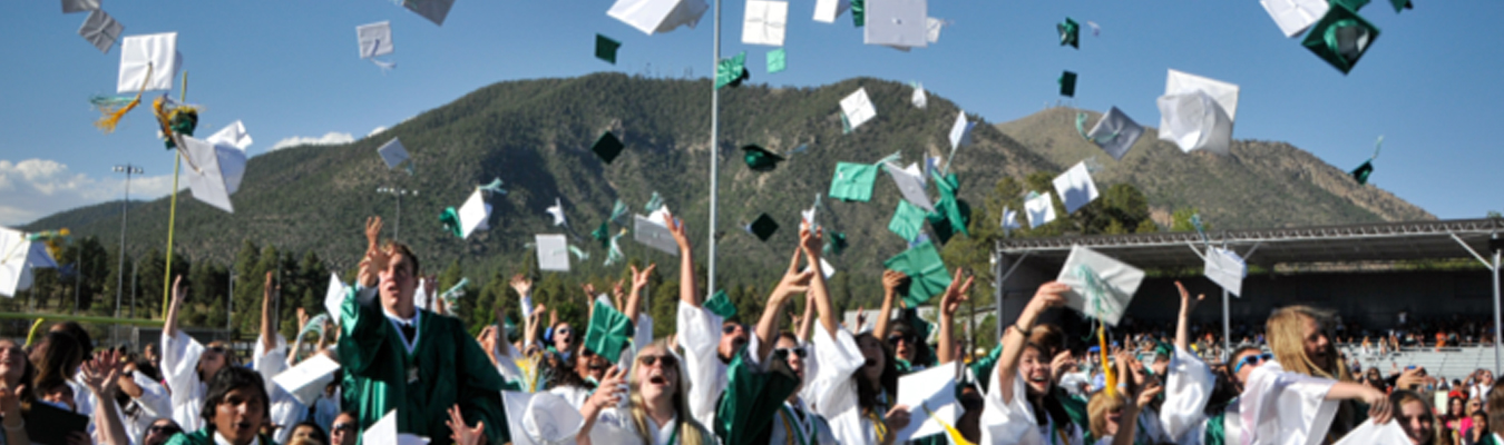 Flagstaff graduates tossing caps in air Mt Elden background LAUNCH Flagstaff