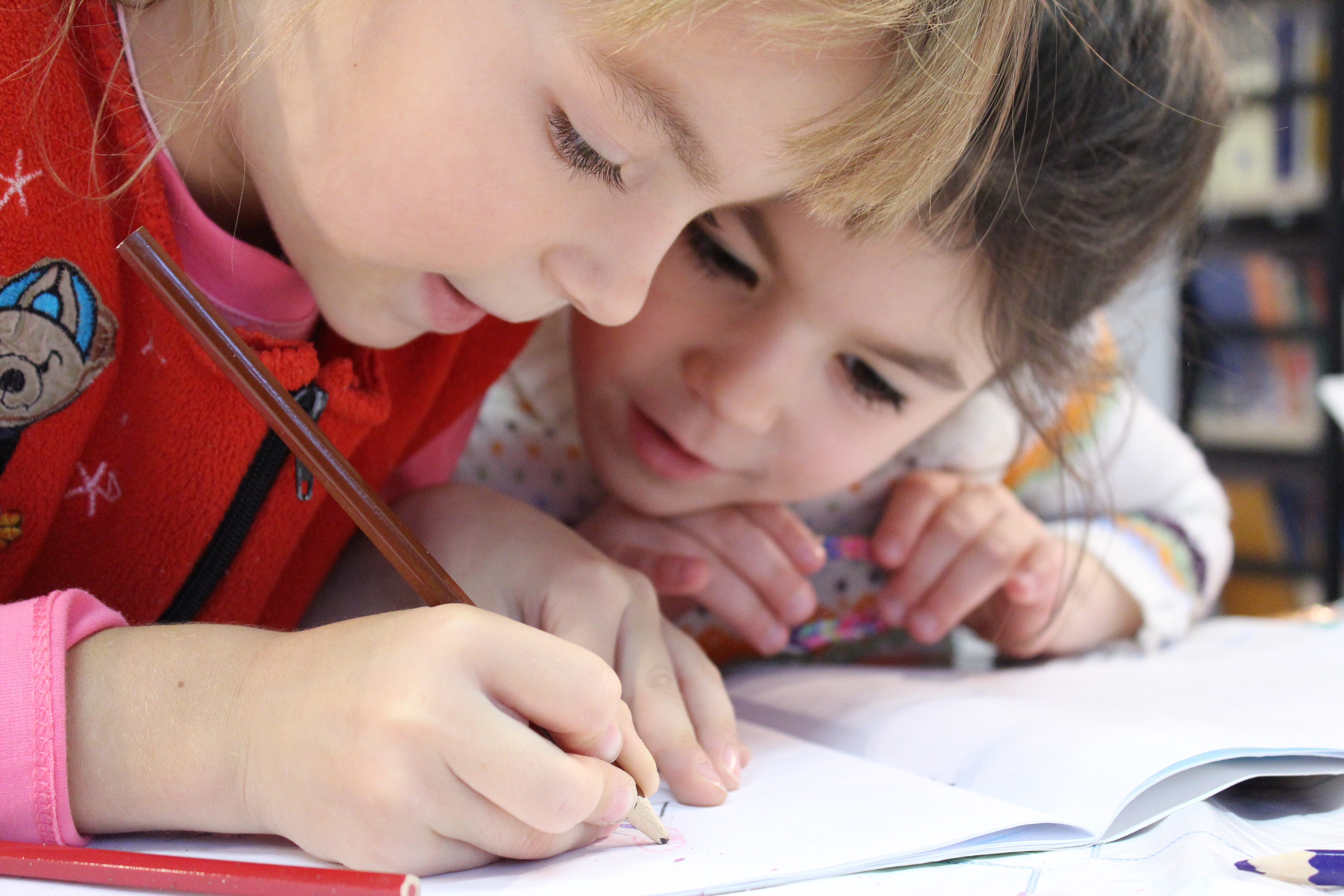 Two young children writing in a book LAUNCH Flagstaff