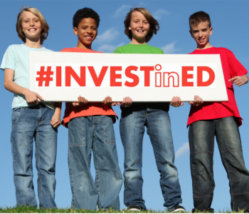Children holding a sign which reads #investined